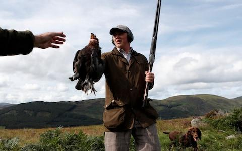 A member of a shooting party holds a hunted grouse on the Rottal Moor on the opening day of the Grouse shooting season on Monday - Credit: RUSSELL CHEYNE/REUTERS
