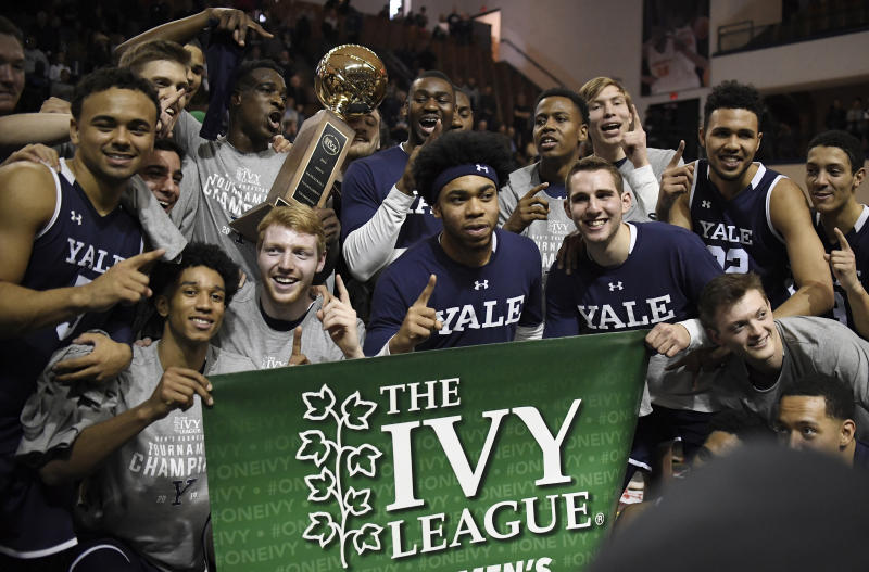 FILE - In this March 17, 2019, file photo, Yale players pose for a photograph with the championship trophy after defeating Harvard in an NCAA college basketball game for the Ivy League championship at Yale University in New Haven, Conn. The Ivy League on Tuesday, March 10, 2020, canceled its men's and women's basketball tournaments because of concerns about the spread of coronavirus. The four-team tournaments were scheduled to be played Friday through Sunday at Lavietes Pavilion in Cambridge. The Ivy League instead will award its automatic NCAA Tournament bids to the regular-season champions, the Princeton women and Yale men. (AP Photo/Jessica Hill, File)