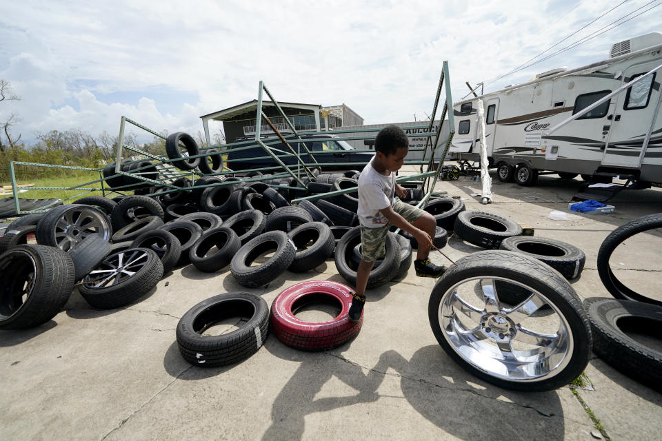 Cameron Arvie, 11, climbs on tires strewn by Hurricane Laura, at the family's destroyed auto detailing business in Lake Charles, La., in the aftermath of Hurricane Laura, Sunday, Aug. 30, 2020. (AP Photo/Gerald Herbert)