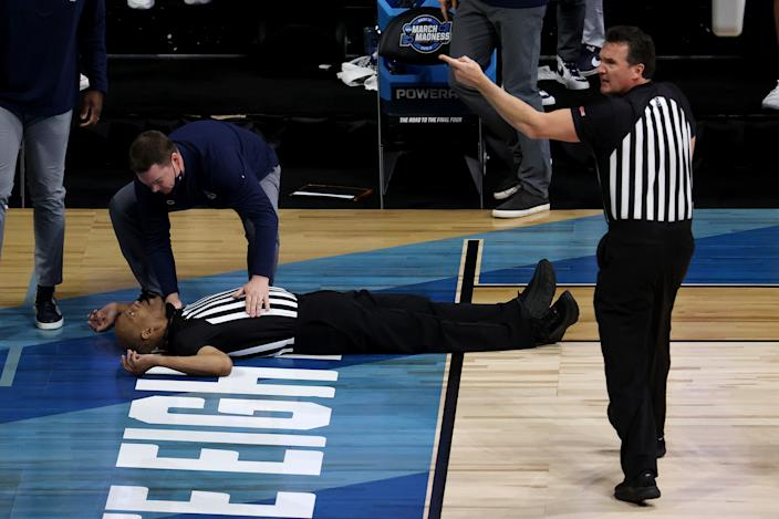 INDIANAPOLIS, INDIANA - MARCH 30: Referee Bert Smith lies on the court after collapsing during the first half of the Elite Eight round game between the USC Trojans and the Gonzaga Bulldogs during the 2021 NCAA Men's Basketball Tournament at Lucas Oil Stadium on March 30, 2021 in Indianapolis, Indiana. (Photo by Andy Lyons/Getty Images)