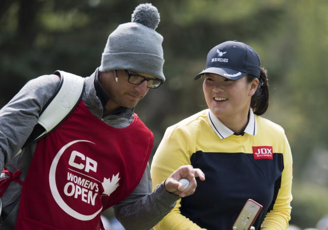 Angel Yin, of the United States, shares a laugh with her caddie on the fifth green during the women's Canadian Open golf tournament in Regina, Saskatchewan, Saturday, Aug. 25, 2018. (Jonathan Hayward/The Canadian Press via AP)