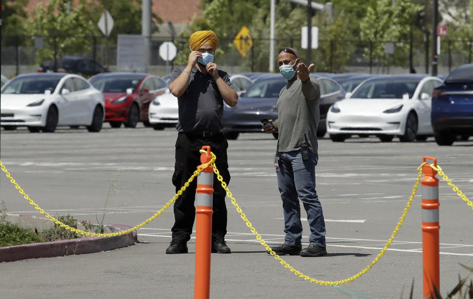 Men don masks as they guard new Tesla vehicles at the Tesla plant Monday, May 11, 2020, in Fremont, Calif. The parking lot was nearly full at Tesla's California electric car factory Monday, an indication that the company could be resuming production in defiance of an order from county health authorities. (AP Photo/Ben Margot)