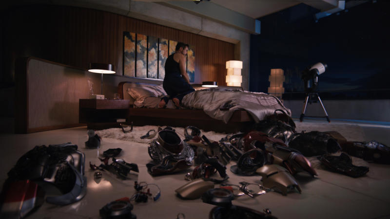 """This undated image provided by Disney-Marvel Studios shows a lamp designed by the late sculptor Isamu Noguchi illuminating Tony Stark's/Iron Man's (Robert Downey Jr.) bedroom in the movie, """"Iron Man 3."""" The lamp's striking geometric design -- a series of irregularly stacked white boxes -- can be seen to the right of the bed. The production designer for """"Iron Man 3,"""" Danielle Berman, says she loves using Noguchi lamps in sets when appropriate because of their linear modernist look and because of the soft glow they emit when lit. (AP Photo/Disney, Marvel Studios, Film Frame)"""