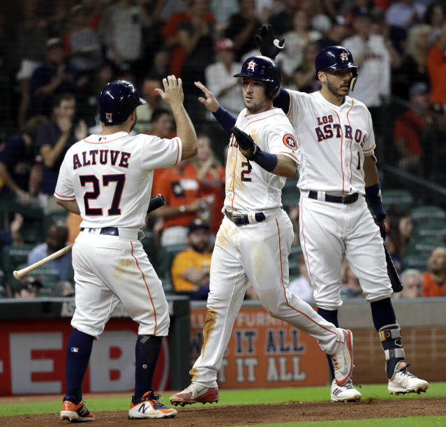 Houston Astros' Alex Bregman (2) and Jose Altuve (27) celebrate after scoring as Carlos Correa (1) waits to bat against the Arizona Diamondbacks during the sixth inning of a baseball game Saturday, Sept. 15, 2018, in Houston. (AP Photo/David J. Phillip)