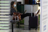 A traveler wears a mask as she waits for her flight in Terminal 3 at O'Hare International Airport in Chicago, Sunday, Nov. 29, 2020. Friday's total of new cases is the next-to-lowest daily number in the past 12 days, but Illinois state officials are bracing for another surge after many people around the country traveled for Thanksgiving and celebrated with family and friends. (AP Photo/Nam Y. Huh)