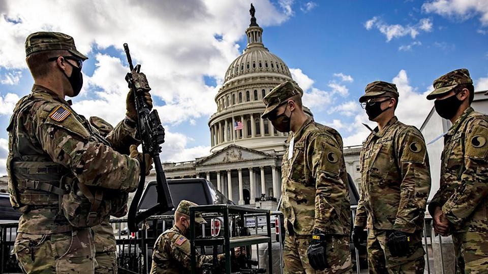 National Guard soldiers are issued their M4 rifles and live ammunition on the east front of the US Capitol - 17 January 2021