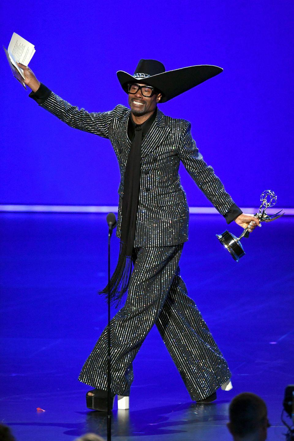 """<p>Collecting his Emmy for Best Lead Actor in a drama series for Pose (and becoming the first, gay, black man to do so), Porter wore a custom Michael Kors pinstripe suit with platform shoes, a Stephen Jones custom hat an extra-long scarf as a tie. </p><p>The actor explained that he wanted a '70s disco throwback moment' with his attire to <a href=""""https://www.hollywoodreporter.com/news/pose-star-billy-porter-what-ill-be-wearing-at-emmys-1240439"""" rel=""""nofollow noopener"""" target=""""_blank"""" data-ylk=""""slk:The Hollywood Reporter"""" class=""""link rapid-noclick-resp"""">The Hollywood Reporter</a>.</p>"""