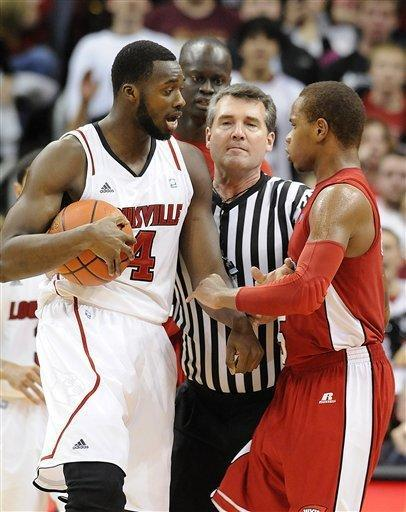 Referee Doug Shows, center, gets between Louisville's Rakeem Buckles, left, and Western Kentucky's Derrick Gordon during the second half of their NCAA college basketball game on Friday, Dec. 23, 2011 in Louisville, Ky. Louisville defeated Western Ky. 70-60. (AP Photo/Timothy D. Easley)