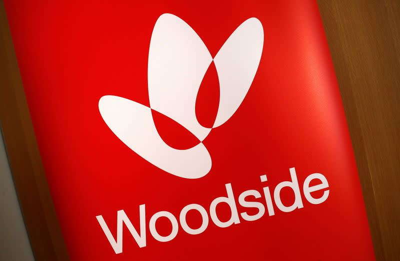 FILE PHOTO: The logo for Woodside Petroleum, Australia's top independent oil and gas company, adorns a promotional poster on display at a briefing for investors in Sydney
