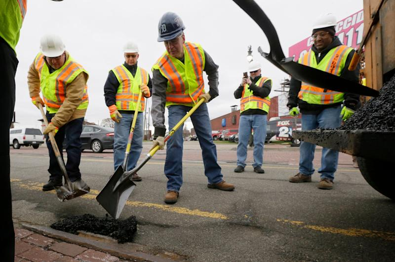 Republican Rick Snyder, Whitmer's predecessor as governor, joined a pothole repair crew one day in 2015 to help promote a sales tax initiative that would have helped finance road maintenance. The initiative failed badly at the polls. (Photo: ASSOCIATED PRESS)