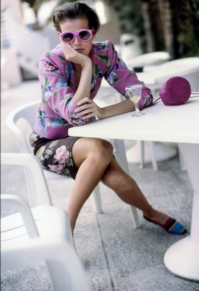 Model Jenny Howarth sitting at a patio table at the Fontainebleau Hilton Resort and Spa in Miami Beach, Florida. She wears a floral printed fitted silk jacket and short skirt, both from Emanuel Ungaro Parallele, pink sunglasses from Christian Lacroix for Optyl Sunglasses, a pink drawstring bag from Prada, and flat color-blocked shoes from Unisa. Hair by Christiaan. Makeup by Sonia Kashuk.