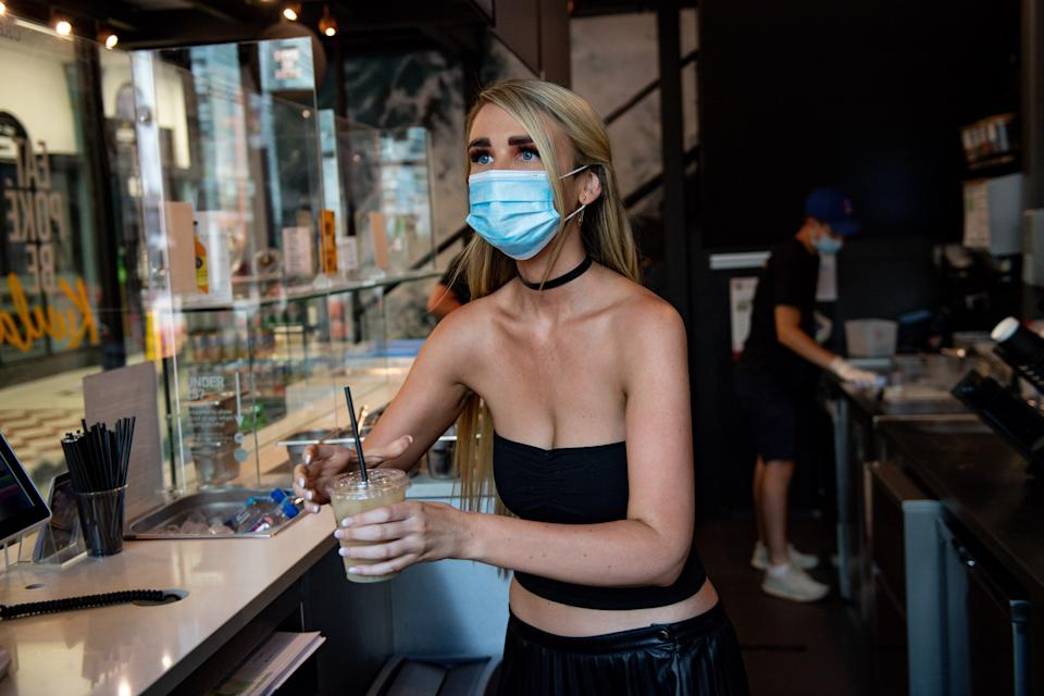 Felicity Whiston, wearing a face mask whilst serving drinks at take away restaurant Kuula Poke in Birmingham, as non-essential shops in England open their doors to customers for the first time since coronavirus lockdown restrictions were imposed in March. (Photo by Jacob King/PA Images via Getty Images)