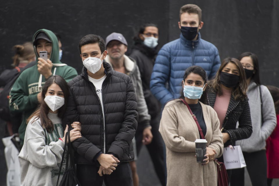 People wear face masks as they watch a street performer in Montreal, Saturday, Oct. 24, 2020, as the coronavirus pandemic continues. (Graham Hughes/The Canadian Press via AP)