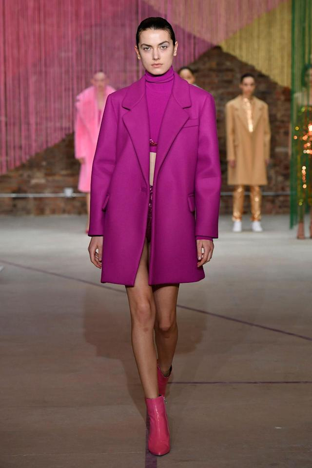<p>Model wears a fuchsia coat, crop top, skirt, and booties at the Milly Fall/Winter 2018 show. (Photo: Courtesy of Greg Kessler) </p>