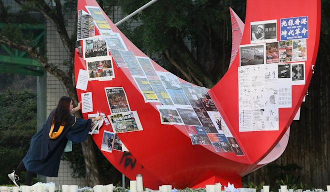 A fresh graduate takes down anti-government posters at the HKUST campus in November. Photo: Felix Wong