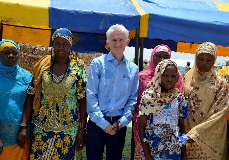This photo taken on September 10, 2017 shows UN Under Secretary-General for Humanitarian Affairs (OCHA) and Emergency Relief Coordinator Mark Lowcock posing with women  at a camp for refugees and internally displaced persons  in southeast Niger