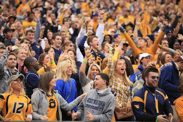 West Virginia fans react to a touchdown during the second quarter of their NCAA college football game against Texas Tech in Morgantown, W.Va., on Saturday, Oct. 19, 2013. Texas Tech won 37-27. (AP Photo/Christopher Jackson)