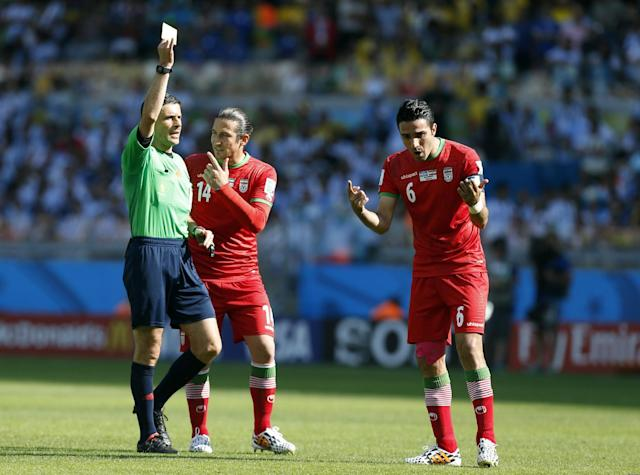 Referee Milorad Mazic from Serbia shows a yellow card to Iran's Javad Nekounam, right, during the group F World Cup soccer match between Argentina and Iran at the Mineirao Stadium in Belo Horizonte, Brazil, Saturday, June 21, 2014. (AP Photo/Jon Super)