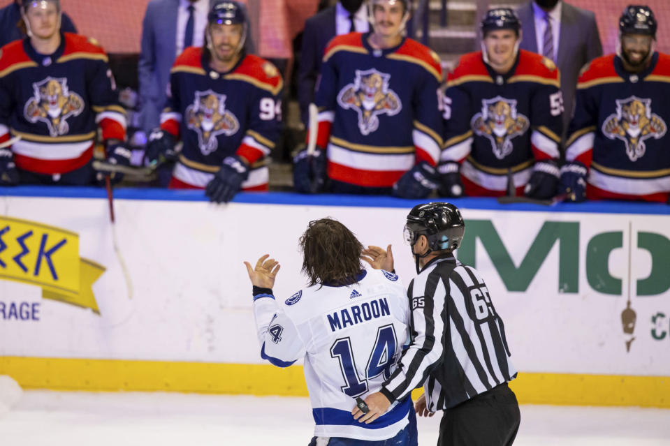 Tampa Bay Lightning left wing Pat Maroon (14) exchanges words with the Florida Panthers bench as he is led off the ice for fighting during the third period of an NHL hockey game on Saturday, May 8, 2021, in Sunrise, Fla. (AP Photo/Mary Holt)