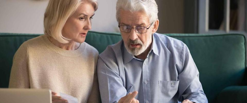 Concerned elderly husband and wife use calculator machine calculate household expenditures