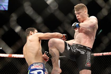 Paul Felder (R) knees at Danny Castillo in a lightweight bout at UFC 182. (Getty)