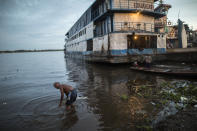 A man bathes in the shallow waters of the Masusa port in Iquitos, Peru, Friday, March 19, 2021, amid the new coronavirus pandemic. In April 2020, the pandemic hit Peru hard, and Iquitos was struggling - to date, the country has seen more 52,000 deaths, 3,200 of them in Iquitos, a city of half a million. (AP Photo/Rodrigo Abd)