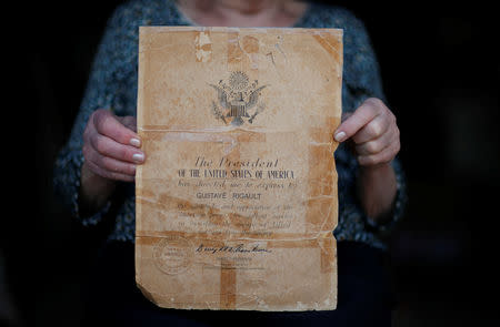Marthe Rigault, 87 years old, from Graignes in the Normandy region holds the letter of gratitude of the American people sent to her father and signed by General Dwight Eisenhower as she attends an interview with Reuters in Graignes, France May 15, 2019. Picture taken May 15, 2019. REUTERS/Christian Hartmann