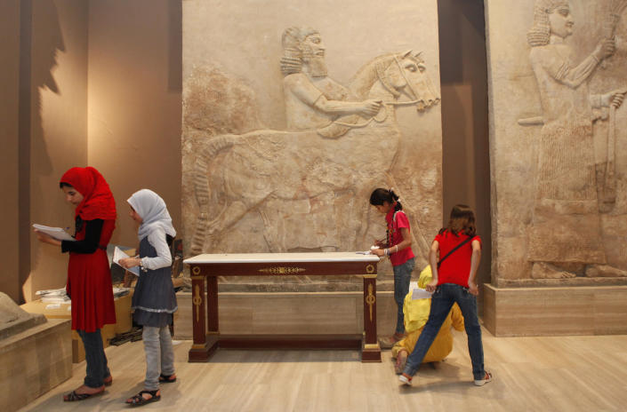 FILE - In this Tuesday, April 2, 2013 file photo, school students visit the restored Iraqi National Museum in Baghdad, Iraq. Ten years after Iraq's national museum was looted and smashed by frenzied thieves during the U.S.-led invasion in 2003 to topple Saddam Hussein, it's still far from ready for a public re-opening. Work to overcome decades of neglect and the destruction of war has been hindered by power struggles, poorly-skilled staff and the persistent violence plaguing the country, said Bahaa Mayah, Iraq's most senior antiquities official. (AP Photo/Hadi Mizban, File)