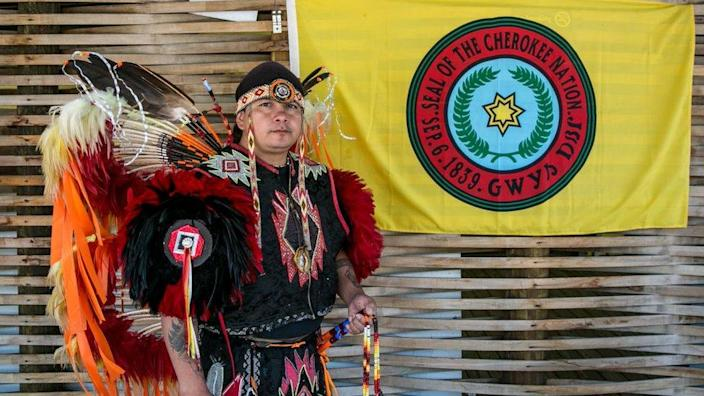 A native American poses by the Cherokee Nation flag