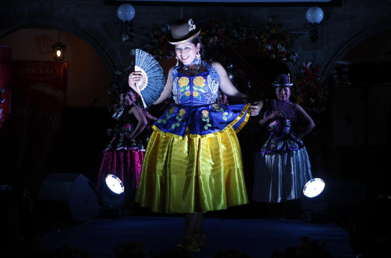 In this Oct. 18, 2013 photo, an Aymara Indian woman models a creation by a local designer at a Chola fashion show in La Paz, Bolivia. The fashion show, designed to promote Andean style and beauty, revived the corset and the traditional petticoat of indigenous Andean women, who are commonly called Cholitas in Bolivian slang. (AP Photo/Juan Karita)