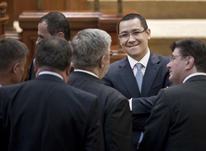 Romanian Premier designate Victor Ponta, right, smiles before a parliament session in Bucharest, Romania, Monday, May 7, 2012. Romanian lawmakers are voting on whether to approve the prime minister designate's left-leaning Cabinet, which is expected to continue a slate of economic reforms. (AP Photo/Vadim Ghirda)