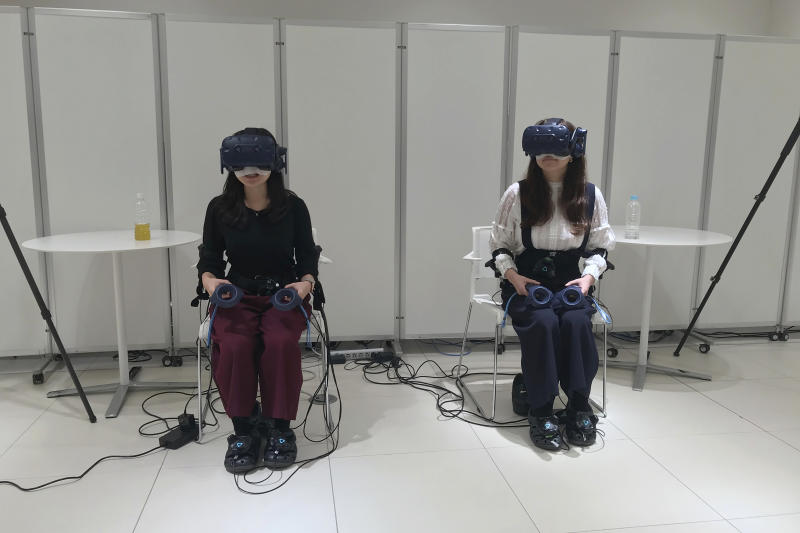 "In this Oct. 18, 2019, photo, people wearing various gadgetry remote control the virtual figures that appear in a car as Nissan demonstrated such technology that is working on at its Oppama test driving course in Yokosuka, near Tokyo. The electric car with smooth four-wheel drive and a virtual friend for the coming age of automated driving are among the technology in development from Nissan. The Japanese automaker is eager to put the scandal over its former star executive Carlos Ghosn behind it. Nissan's newly developed ""all-wheel-control"" technology delivers a sense of greater control and safety. (AP Photo/Yuri Kageyama)"