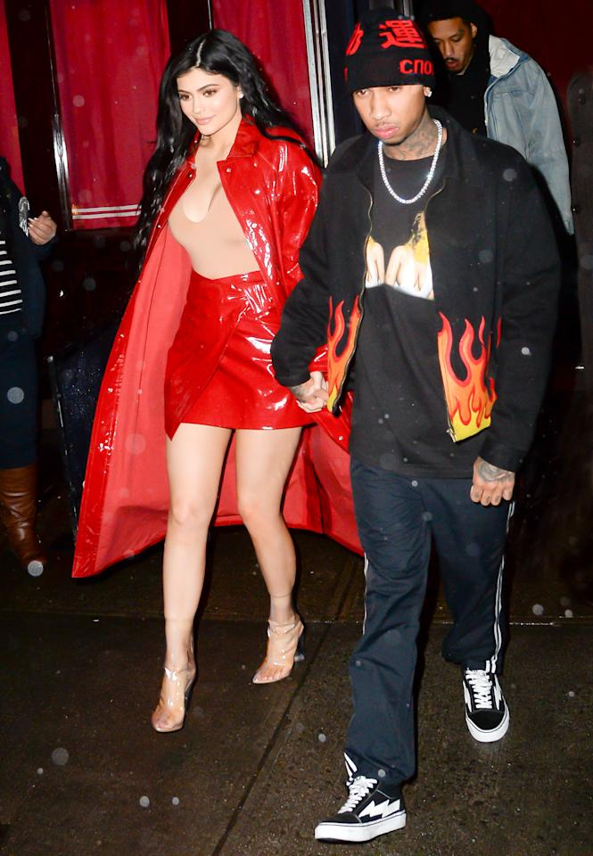 <p>For a night out with boyfriend Tyga, the star grabbed attention in a patent red skirt and matching trench coat that she paired with a plunging nude bodysuit. Clear heeled booties finished off her outfit.</p>