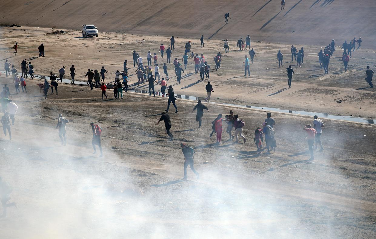 Migrants run from tear gas released by U.S border patrol, near the border fence between Mexico and the United States in Tijuana, Mexico, Sunday. (Photos: Hannah McKay/Reuters)