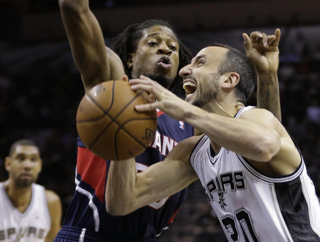 San Antonio Spurs' Manu Ginobili,right, of Argentina, is defended by Atlanta Hawks' Cartier Martin, left, as he drives to score during the first half of an NBA basketball game, Monday, Dec. 2, 2013, in San Antonio. (AP Photo/Eric Gay)
