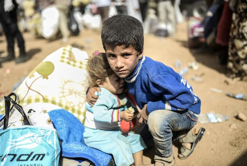 A Syrian boy holds a baby as Kurds, fleeing an onslaught by the jihadist Islamic State group, cross the border into Turkey at the southeastern town of Suruc on September 27, 2014 (AFP Photo/Bulent Kilic)