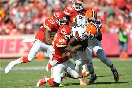 Cleveland Browns wide receiver Josh Gordon (12) is tackled by Kansas City Chiefs cornerback Brandon Flowers (24) and strong safety Eric Berry (29) during the second half at Arrowhead Stadium. The Chiefs won 23-17. Mandatory Credit: Denny Medley-USA TODAY Sports