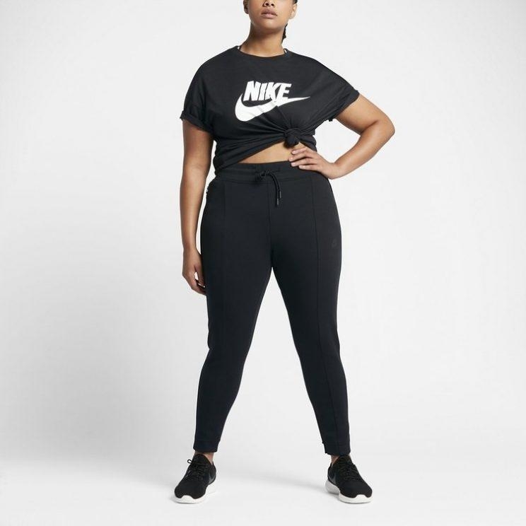 A model wears a black Nike T-shirt, black sweatpants, and black running shoes.