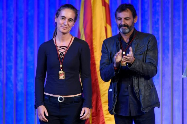 Migrant rescue ship captain Carola Rackete is given a medal from Catalonia's regional parliament alongside Proactiva Open Arms founder Oscar Camps