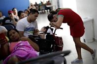 Gleyse Kelly da Silva, 28, rests on the baby carriage of her two-year-old daughter Maria Giovanna, while waiting for a medical appointment in a hospital in Recife, Brazil, August 8, 2018. REUTERS/Ueslei Marcelino/Files