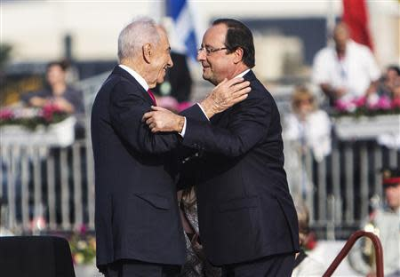 French President Francois Hollande (R) and his Israeli counterpart Shimon Peres greet each other during the official reception upon Hollande's arrival at Ben Gurion airport near Tel Aviv November 17, 2013. Hollande arrived on Sunday for a three-day state visit to Israel and the Palestinian Territories. REUTERS/Nir Elias