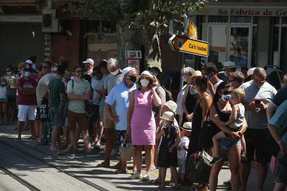 Tourists wait to board a tram in town of Sóller in the Balearic Island of Mallorca, Spain, Monday, July 27, 2020. Britain has put Spain back on its unsafe list and announced Saturday that travelers arriving in the U.K. from Spain must now quarantine for 14 days. (AP Photo/Joan Mateu)