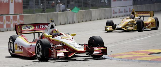 Helio Castroneves, left, of Brazil, races in front of Ryan Hunter-Reay, right, during practice for the IndyCar Grand Prix of Houston auto race, Friday, Oct. 4, 2013, in Houston. Practice was delayed due to surface issues in turn one. (AP Photo/David J. Phillip)