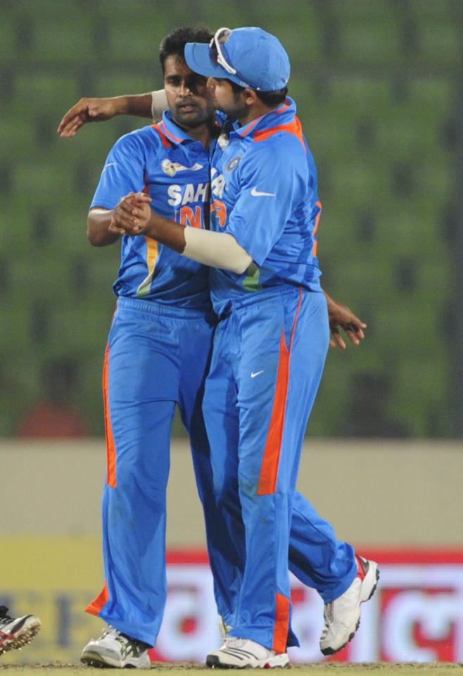 Indian cricketer Suresh Raina (R) congratulates teammate Vinoy Kumar (L) after the dismissal of Sri Lankan batsman Nuwan Kulasekara during the one day international (ODI) Asia Cup cricket match between India and Sri Lanka at The Sher-e-Bangla National Cricket Stadium in Dhaka on March 13, 2012. AFP PHOTO/Munir uz ZAMAN (Photo credit should read MUNIR UZ ZAMAN/AFP/Getty Images)