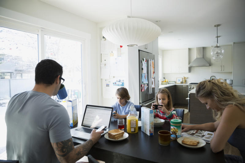 A file picture shows a disengaged family with kids on devices, a father on a laptop and a mum reading a magazine. Source: Getty, file.