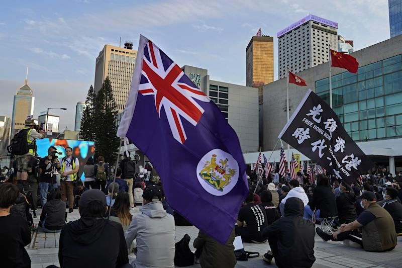 Protesters carry a Hong Kong flag and a flag that reads 'Hong Kong Independence'