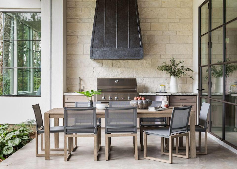 """<p>Houston-based designer <a href=""""http://marieflaniganinteriors.com"""" rel=""""nofollow noopener"""" target=""""_blank"""" data-ylk=""""slk:Marie Flanigan"""" class=""""link rapid-noclick-resp"""">Marie Flanigan</a> says she designed this outdoor area to be an extension of the home's interior space. A grill, sink, and fridge are right at your fingertips, while the rest of the kitchen is just a few steps away behind the glass. An antique bronze hood range and limestone wall complement the interior design.</p><p>This setup not only helps you perfect outdoor living, it's also ideal for those desiring more space for cooking, eating, and entertaining year-round. </p>"""