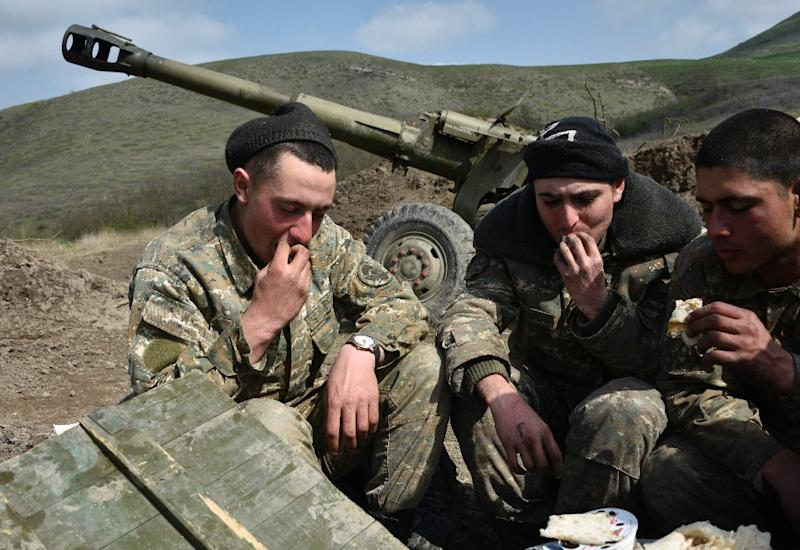 Soldiers of the defense army of Nagorny Karabakh eat by their gun at an artillery position outside the village of Mataghis (AFP Photo/KAREN MINASYAN)
