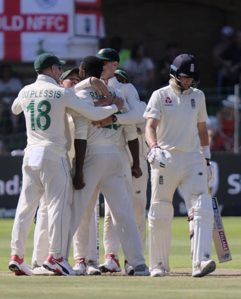 Faf du Plessis of South Africa, left congratulates Kagiso Rabada of South Africa, centre left, on taking the wicket of England's Joe Root, right, during day one of the third cricket test between South Africa and England in Port Elizabeth, South Africa, Thursday, Jan. 16, 2020. (AP Photo/Michael Sheehan)