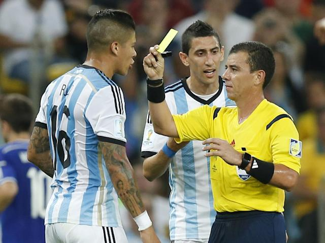 Referee Joel Aguilar from El Salvador gives a yellow card to Argentina's Marcos Rojo, left, during the group F World Cup soccer match between Argentina and Bosnia at the Maracana Stadium in Rio de Janeiro, Brazil, Sunday, June 15, 2014. (AP Photo/Victor R. Caivano)